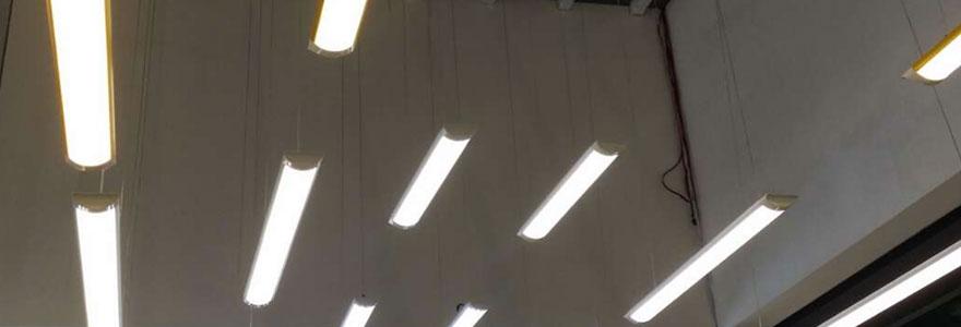 Plusieurs réglettes LED lumineuses suspendues au plafond d'un espace industriel